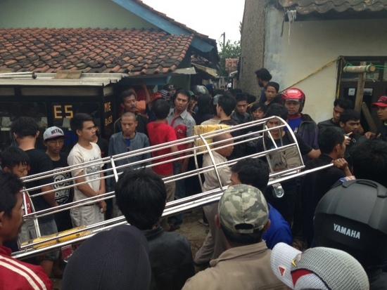 A keranda is carried to the scene accompanied by body bags