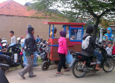 A man sells ice cream to the gathered crowd